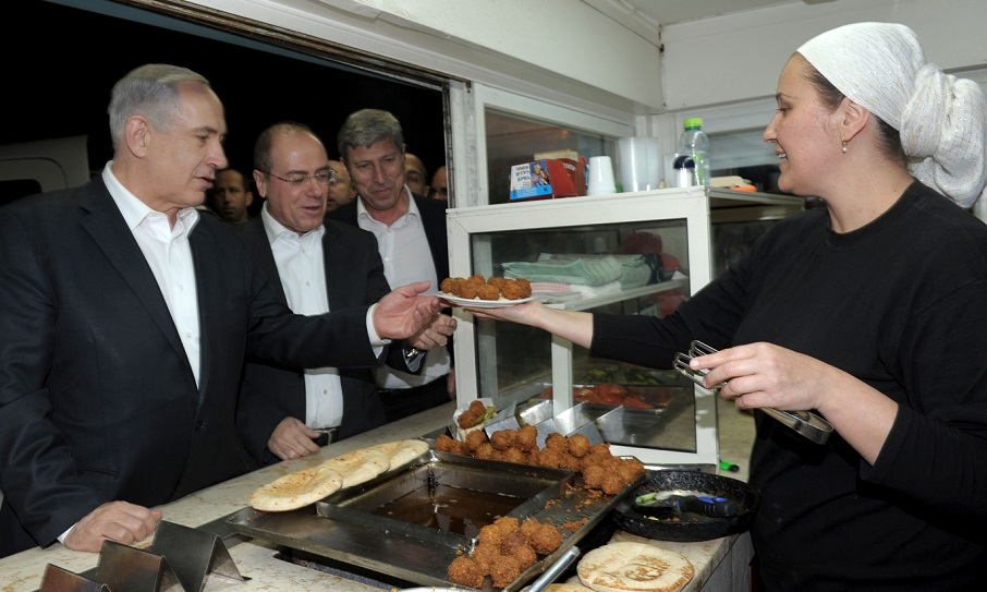 El primer ministro de Israel, Benjamin Netanyahu, recibiendo un plato de falafel en Akko