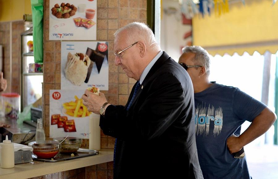 El presidente de Israel, Reuven Rivlin, comiendo con gusto unos falafel en pita